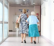 Older lady walking down hospital hall